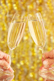 Glasses of champagne in the hands, on the blurred background — Stock Photo