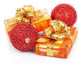 Christmas gift boxes with gold ribbon and red balls on white — Stock Photo