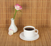 Vase with a rose and a cup with drink against a bamboo cloth — Stock Photo