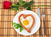 Festive a breakfast on Valentine's Day, sausage in the form of heart, red rose on a bamboo napkin — Stockfoto