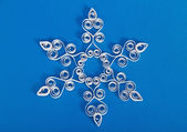 Snowflake with quilling on blue background. Stripe paper swirl — Stock Photo