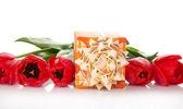Ljusa presentförpackning med en båge och tulpanerna isolerad på vit — Stockfoto