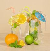 Dos vasos con bebidas, una jarra y un cítrico en una mesa — Foto de Stock