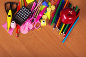 Set of bright office tools and red apple on a table — Stock Photo