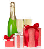 Three gift box with a tape and bow, bottle of champagne and the wine glasses isolated on white — Stock Photo