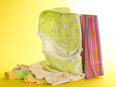 Gift package and baby clothes, on a yellow background — Stock Photo