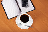 Open notepad, the handle, the calculator, cup of coffee, saucer and spoon on a table — Stock Photo