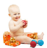 Rapt child holds red christmas ball, festive boxes, colorful red and blue balls isolated on white — Stock Photo