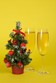 Small Christmas fir-tree in a pot, and two wine glasses with champagne on a yellow background — Stock Photo