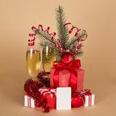 De giften van kerstmis, speelgoed, klatergoud, fir-boomtak, champagne en lege kaart, op een beige achtergrond — Stockfoto