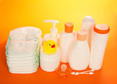 Baby care objects. Olive, shampoo, diapers on an orange background — Stock Photo