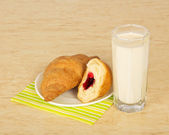 Croissants on a striped napkin and a milk glass, on a table — Stock Photo