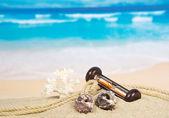 Sea cockleshells, hourglasses and a rope on sand — Stock Photo