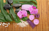 Monstera leaf, orchid and set for Spa on a bamboo cloth — Stock Photo