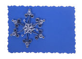 Quilling. Made of strips of paper snowflake on blue xmas card isolated on white — Stock Photo