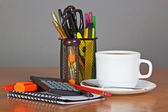 Blank sheets for notes, a set of office supply in a support and a cup of coffee on a table — Stock Photo