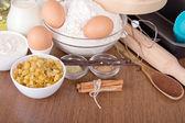 Flour, milk, sour cream and eggs, raisin, sesame, vanilla and cinnamon on a table — Stock Photo