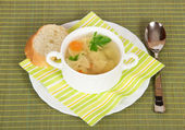 Bowl with soup, bread, a plate, a spoon and a napkin on a green bamboo cloth — Stock Photo