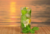 Glass with a mojito and a spearmint leaf, on a bamboo cloth against the sunset — Stock Photo