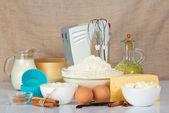 Set of products for baking, a mixer and a cake pan against a canvas — Stock Photo