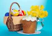 Eggs in a basket with a napkin, an Easter cake and a vase with narcissuses, on the blue — Stock Photo