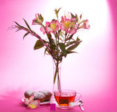 Appetizing cupcake on a dish, tea and an alstroemeria in a vase, on a pink background — Stock Photo
