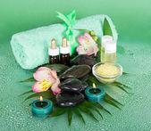 Steine, Salz, Kerzen und ein Handtuch mit einem Band auf einem grünen Hintergrund — Stockfoto