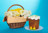 Basket with white and yellow narcissuses, an Easter cake and marzipan chickens, on the blue — Stock Photo