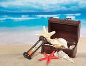 Ancient chest with sea cockleshells, hourglasses on sand — Stock Photo