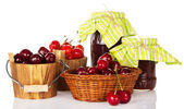 Different grades of sweet cherry in buckets, a basket with sweet cherry and jars of jam — Stock Photo