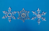 Three paper Christmas snowflakes, self-made. On blue background — Foto Stock