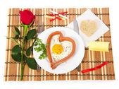Valentine's Day. Sausage in the form of heart, fried egg, bread, red rose, notes with prediction on a bamboo napkin — Stock Photo