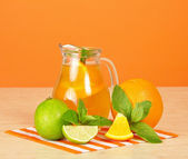 Orange drink, citrus, mint and striped napkin on a table — Stock Photo