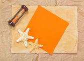 Old paper, two starfishes, hourglasses and orange card — Stock Photo