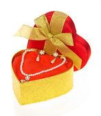 Collier et boucles d'oreilles en or coffret en forme de coeur avec ruban d'or et archet isolé sur blanc — Photo