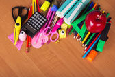 Set of bright office tools, an exercise books and apple on a table — Stock Photo