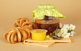 Cup of tea, honey, jam bank, a linking of bagels, flowers and a napkin on the beige — Stock Photo