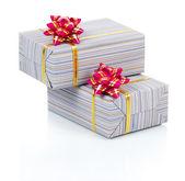 Coffrets cadeaux avec un ruban or et rose bow isolé sur blanc — Photo