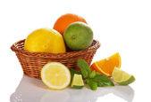 Citrus in a wicker basket, slices of fruit near a basket, mint — Stock Photo
