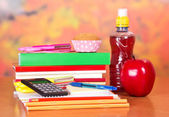 A set of school accessories, bottle with drink, cake and apple — Stock Photo