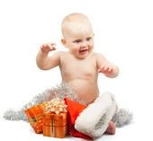 Bambino felice con tinsel argento Natale, cappello di Babbo Natale rosso e scatole regalo luminose isolate su bianco — Foto Stock