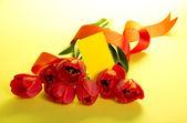 букет из тюльпанов, украшенные лентой и пустой карты для текста на желтом фоне — Стоковое фото