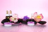 La valeur des huiles parfumées, sels, bougies, pierres, un nat, sur un fond rose — Photo