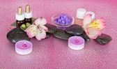 Bougies et huile arôme, sel, pierres et un flowe, sur un fond rose — Photo