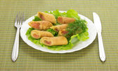 Pancakes with salmon and salad, cutlery on green napkin — Stock Photo