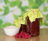 Jars of jam, a cup of sugar and handful of berries on a table — Stock Photo