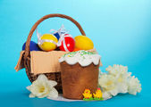 Easter cake, marzipans, flowers and basket with eggs, on a blue background — Stock Photo