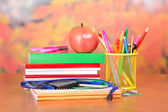 Books, pencils and handles in a support, a pencil-case, a scissors and apple, on a table — Stock Photo