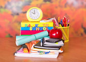 A set of school accessories, the calculator, alarm clock and red apple on a table — Photo