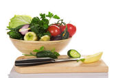 Bowl with vegetables, a chopping board and the knife — Stock Photo